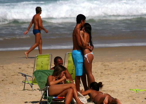 A boy tries to hug a girl at the beach in Ipanema beach in Rio de Janeiro ...
