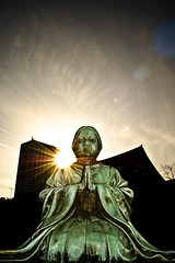 Zojoji Statue Praying (Francis Mueller) Tags: city trip travel sunset vacation sun holiday green art silhouette yellow statue japan outside temple tokyo outdoor buddhist religion praying buddhism flare zojoji sunflare nikond40