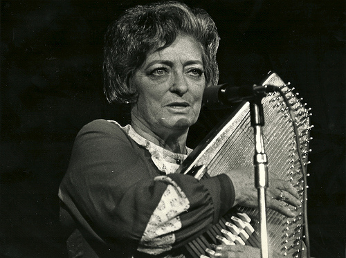 Mother Maybelle Carter at a microphone stand playing the autoharp