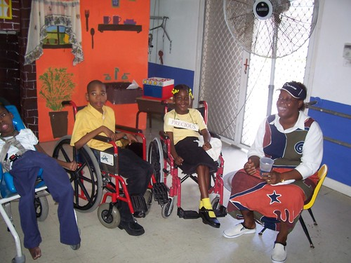 Three children in wheelchairs, smiling at the camera. An adult is seated to their right. One of the walls in the room is brightly coloured, with a mural of a household scene painted on it.