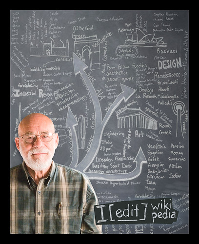 Art historian in front of blackboard covered in writing describing aspects of Wikipedia with key phrase - I EDIT Wikipedia