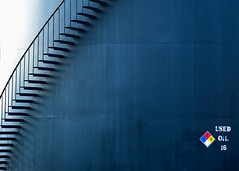 Spiral Staircase on the Side of Storage Tank (Todd Klassy) Tags: blue shadow abstract color colour lines metal horizontal wisconsin stairs dark spiral fossil steel label painted steps nobody storage stairway used container business madison staircase installation oil environment products 16 petrol copyspace industrialpark recycling hue wi fuel sixteen external spiralstaircase globalwarming linear fueltank storagetank internal stockphoto welded madisonwisconsin petroleum floatingroof gallons stockphotography refining cylindrical aboveground litres petrochemical colorimage oilrefineries liters tankfarm number16 oilindustry oildepot oilterminal usedoil fuelstorage pressurevessels madisonphotographer industrialfuel toddklassy oilproductionplant oilstoragetrade motoroilrecycling dream16