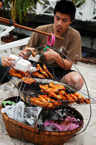 At lending a hand at grilling chicken, Ko Samet