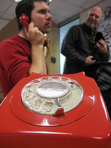 man making call with vintage red rotary phone