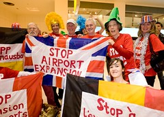 Local MP John McDonnell joins anti-aviation campaigners with the flags of the other protesting nations at Heathrow Terminal One to demonstrate against the 3rd runway and aviation expansion. by Euroflashmob Heathrow and Europe