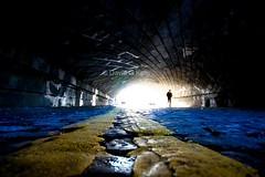 The Spy Who Came In From The Light (Dave G Kelly) Tags: road bridge ireland light dublin silhouette mystery underpass tunnel cobblestones figure spy doubleyellowlines yellowstripes lightroom lightattheendofthetunnel blueribbonwinner mywinners artlibre platinumheartaward davegkelly