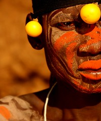 (Tribal) Perspective (Nomadic f-stops) Tags: africa portrait orange face yellow eyes mask perspective lips exotic ethiopia facepaint mursi africanportrait mursitribe southernethiopia magonationalpark ethiopiantribe ethiopianethnic mursiman ethiopianportrait mursiportrait