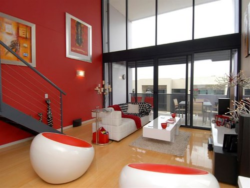 Luxury-modern-living-room-with-red-walls-sofa-and-coffee-table-furniture-and-staircase