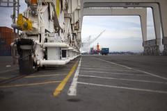 Untitled (Andrew Schrer) Tags: zeiss port t concrete oakland cranes asphalt containers planar gantry portofoakland intermodal planart gantrycranes
