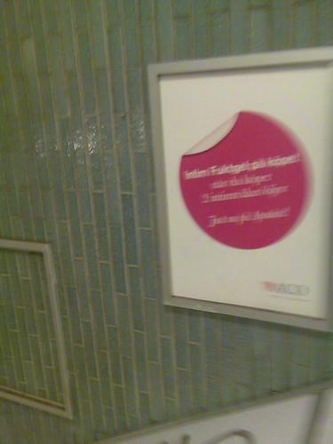 Annonstavla i en tunnelbanenedgång med en lila cirkel i mitten med vit flik överst till vänster och med texten 'Intim Fuktgel på köpet när du köper 2 intimtvålar/oljor Just nu på Apoteket!'