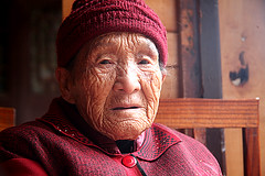 kIMG_5190 (Sam's Exotic Travels) Tags: red woman senior river sam coat cobblestones aged ethnic wrinkles sams bluestone stockingcap residents theface tuja mengdong mywinners wangcun exotictravelphotos exoticphoto wangcuntown