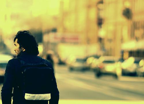 Fotografía de un chico alejándose con una mochila a las espaldas con un anaranjado panorama por delante