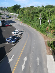 Good view of a parking garage access road from the topmost level of the parking garage it accesses. In Schenectady. (Tim Kiser) Tags: 2016 20160829 august august2016 capitaldistrict capitalregion img7811 mohawkvalley newyork newyorkstate newyorklandscape schenectady schenectadycounty schenectadycountynewyork schenectadymunicipalparking schenectadynewyork schenectadylandscape schenectadymunicipalparkinggarage schenectadymunicipalparkingramp accessdrive accessroad arrows bidirectionalarrow bidirectionaldrivinglane cars dashedwhiteline differentkindsofpavement doubleyellowline downtown downtownschenectady driveway easternnewyork easternnewyorkstate electricpoles landscape mostlysunny multidirectionalarrow multidirectionaldrivinglane overgrown overgrownarea parkedcars parkinggarage parkinggarageaccessroad parkinggaragedriveway parkinglots parkingramp parkingrampaccessroad parkingrampdriveway paved pavement reversiblelane reversibletrafficlane roadmarkings sunnylandscape telephonepoles trafficlanes twodirectionalarrow upstatenewyork upstatenewyorklandscape urbanlandscape utilitypoles view viewfromaparkinggarage viewfromaparkingramp unitedstates
