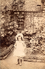 Tiny child in wonderful Edwardian back garden (lovedaylemon) Tags: vintage garden found child image boots path morningglory bonnet hollyhock edwardian boxhedge