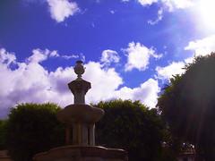 Fuente de La Plaza del Adelantado (Edu Martnez) Tags: plaza sky white verde love sol azul clouds square sadness gris rboles amor fuente cielo plazas nubes tenerife font laguna estatua fontana hapiness manteca lalaguna rayos ojodebuey adelantado centellas pandelea