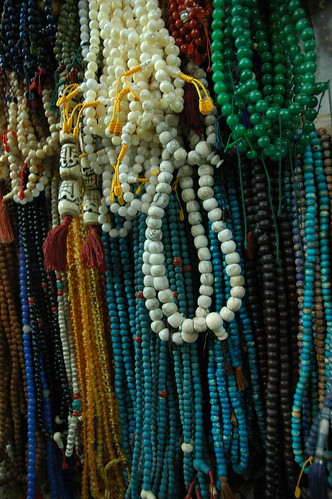Blue, green, gold, and white, bone mala beads, head beads, guru beads, mala makers and sellers, at the wish fulfilling Great Stupa. Boudha, Kathmandu, Nepal by Wonderlane