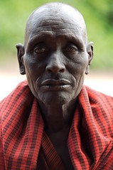 Masai (jerikojosh) Tags: africa old travel red portrait beauty closeup contrast digital canon tanzania saturated colorful village bokeh african vibrant candid thoughtful streetphotography safari warrior 5d massai spiritual masai villager villagelife 70200mmf28l jerikojosh smallmonk