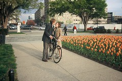 Two Lips (Michael Ronquillo) Tags: flowers bike bicycle washingtondc still couple candid strangers streetphotography slidefilm nocrop 2007 foggybottom anybodyknowwhatkindofflowers inbetweenkisses aretheytulips bymichaelronquillo michaelronquillophotography