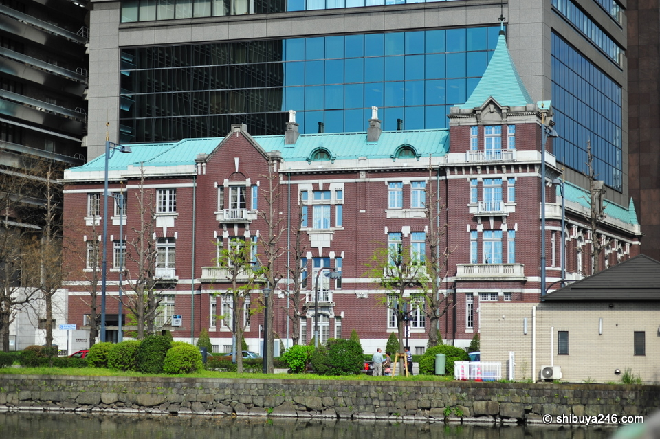 One of the many older buildings around Tokyo Station which as been preserved and incorporated into the development of a new taller building. Can you see the old building roof meeting the new glass building on the right side?