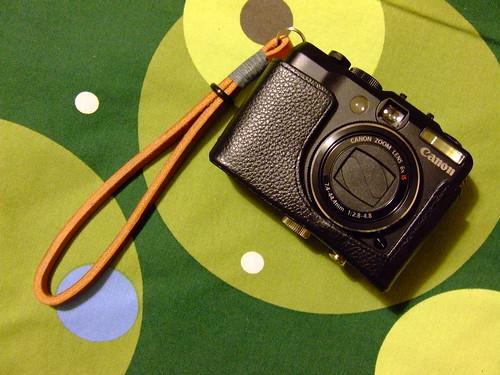 Foto de mi cámara con funda de cuero y correa a juego sobre colcha de IKEA