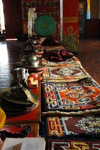Where the community of monks sit, pecha (prayer book), mala, cymbals, tea cup, little carpets, robe, drum, horns, khatas, wish fulfilling jewel mural, dorjes, bells, polished wood floor, Pharping Sakya Monastery, Nepal by Wonderlane