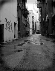 A Little Dog Barks His Head Off in the Distance (redmann) Tags: urban blackandwhite bw toronto ontario canada reflection canon puddle graffiti alley sigma bleak disused stark puddles grotty grot seamy thecontinuum yersister sigma18200dc canon400d anawesomeshot aplusphoto artlegacy