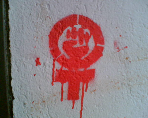 A graffiti in red ink on a white wall of the feminist power fist.