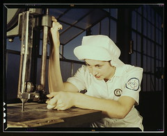 """Women in white"" doctor Navy planes (motors) at the Naval Air Base, Corpus Christi, Texas. Mildred Webb, an NYA trainee at the base, is learning to operate a cutting machine in the Assembly and Repair Department. After about eight weeks as an apprentice s"