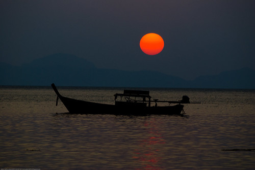 Longtail boat at sunset at Ting Rai Bay, Koh Jum, Thailand by Adam Cathro.