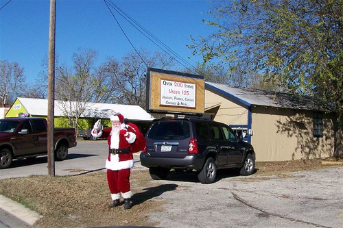 The florist shop picked a very authentic looking Santa. Must be hot today in that suit; it's a warm day.