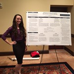 A student posing with her research poster