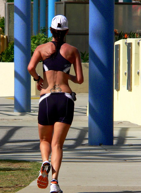 Tattoo running. a jogger along the beach side path at Redcliffe.