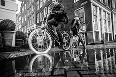 Cycling through puddle @ Amsterdam (PaulHoo) Tags: fujifilm x70 fuji amsterdam holland reflection city urban people candid streetcandid citylife 2017 bw blackandwhite monochrome bike bicycle low pov contrast puddle water building tourism rain weer weather