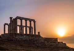 The Temple of Poseidon at Dusk, Cape Sounion, Greece (Bathsheba 1) Tags: light sunlight seascape reflection history nature water architecture reflections landscape geotagged evening ancient nikon scenery rocks colours view eveningsun scenic dramatic vivid peaceful calm greece cape naturalbeauty lightandshadow tranquil sounion greektemple 2014 nikond3200 glowinglight aegeansea templeofposeidon pastelcolours d3200 greekgodofthesea vision:sunset=0835 vision:sky=0828 vision:outdoor=0959 attikipeninsula