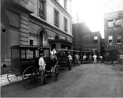 Parcel Post Wagons in Knoxville, TN (Smithsonian Institution) Tags: city horses urban blackandwhite men brick cars wagon streetscene usps buggies carriages smithsonianinstitution oldreliable usmail carriges mailmen nationalpostalmuseum parcelpost printingshop mailscreenwagons parcelpostservice