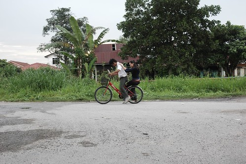 Ali (Arshad Zamir) giving Miss Carol (Carmen Soo) a ride on his bicycle
