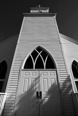 First Baptist Tower (Tom Haymes) Tags: windows shadow blackandwhite bw white building church window architecture rural blackwhite texas katy cross country gothic churchtower symmetry historic belltower steeple countrychurch firstbaptistchurch top20texas assignmenthouston21
