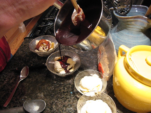 Pouring hot fudge sauce on the ice cream dessert
