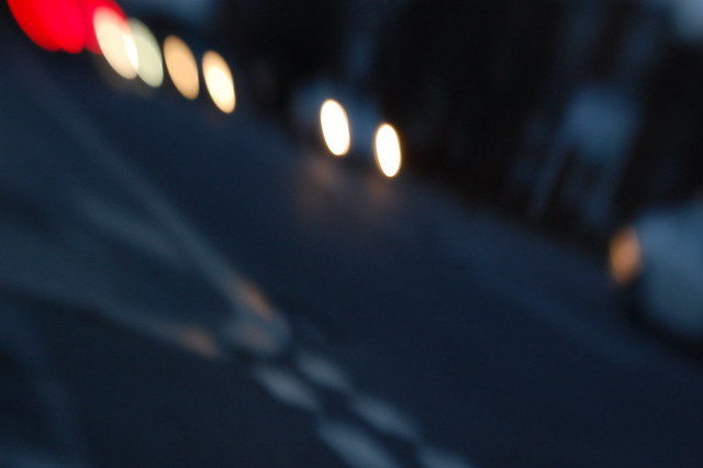 A blurry shot of a road junction with oncoming car lights