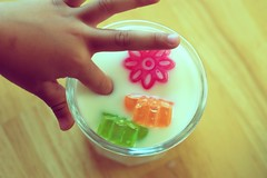 Playing with Food (: c a l v i n a :) Tags: wood pink orange yellow limegreen m snack floatingice iceshapes woodentable september2007 glassofmilk handinmilk