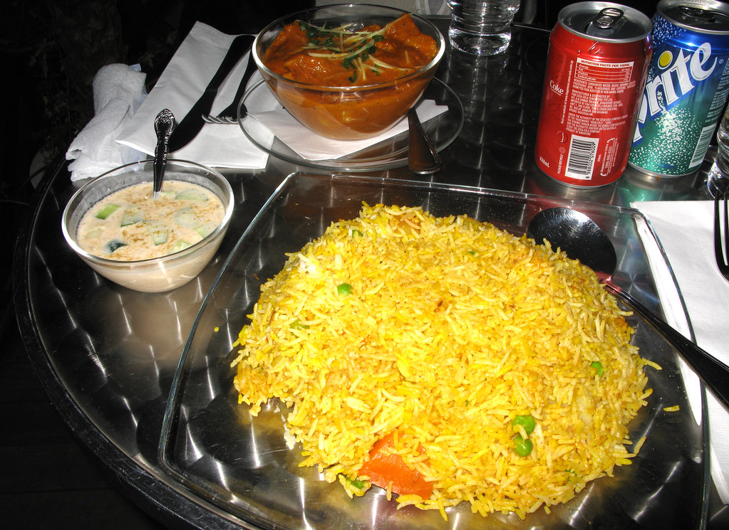 Tikka & Biryani - Vegetarian Zafran biryani and yogurt sauce, Aloo Gobi in the background