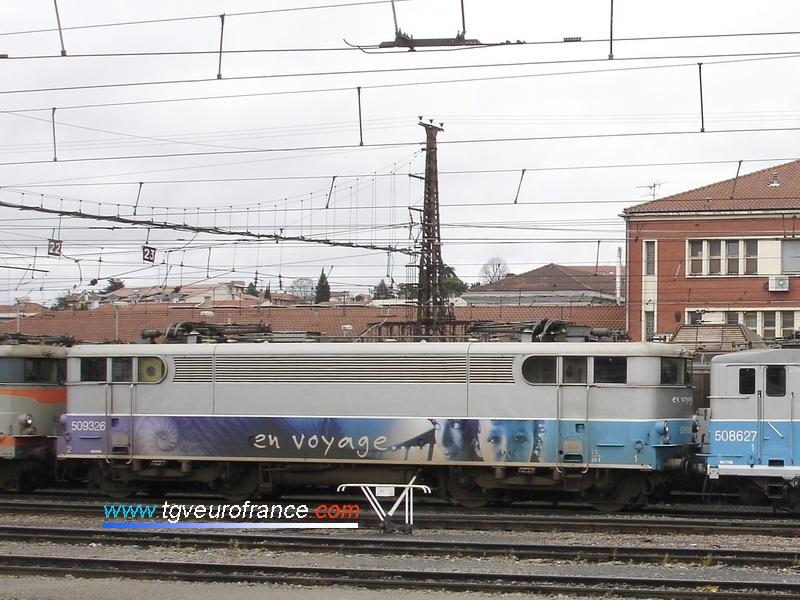 """Une locomotive électrique BB9300 SNCF en livrée """"En voyage"""" stationne sous caténaire 1500 V."""