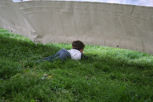 Kid peering under music tent