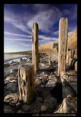 'Poles Apart' - Jersey (jerseyimage) Tags: wood greatbritain blue sea sky color colour tourism beach wall clouds canon outside outdoors coast wooden sand raw day britishisles vivid sunny explore coastal jersey granite poles february dslr posts upright railings channelislands stumps verticle lateafternoon stouen stouensbay channelisles 400d jerseyimage