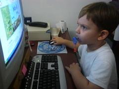 joão pedro, 4 anos, de chupeta, brincando no computador