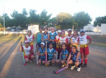Jugadoras de la Esc. Municipal de Hockey Hdo. -con remera blanca y roja-