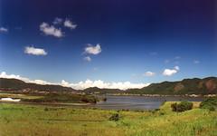 Piratininga lagoon (Rodrigo Neves - Catching up with your great work s) Tags: blue brazil water grass rio brasil clouds rj 28mm deep bluesky lagoon hills zenit lagoa polar polarizer niteroi piratininga 12xp mywinners