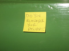 Yellow post-it note with 'did you remember your passport?' written on it and stuck to a green background