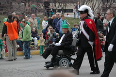 An old warrior rolls on. (kennethkonica) Tags: red people irish orange usa white black tiara men sunglasses outdoors women shoes sitting indianapolis seat wheels watching feathers hats parades bowtie indiana capes gloves sit uniforms seated crowds derby stpatricksday onlookers wheelchairs amputees legless dressedinblack greenclothes sheads indianapolisstpatricksdayparade