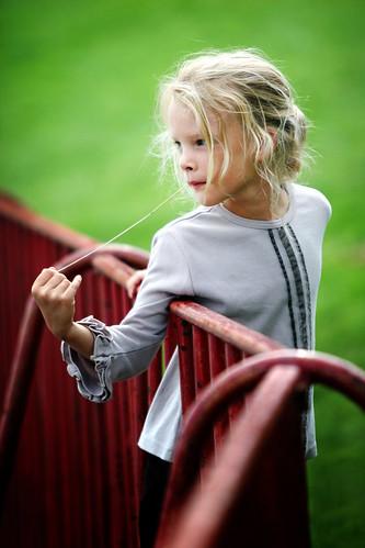 Une petite fille appuyée à une barrière rouge semble perdue dans ses pensées.